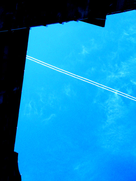 the legislature in victoria frames the vapour trail of a jet plane flying high overhead..
